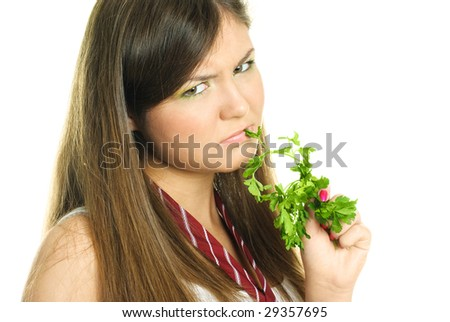 portrait of an unhappy beautiful brunette girl eating fresh green parsley - stock photo