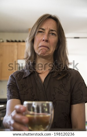Portrait of an unhappy middle aged woman in the kitchen drinking wine. - stock photo