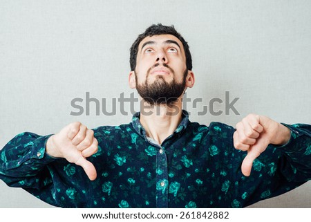 Portrait of an unhappy young man with thumbs down sign - stock photo