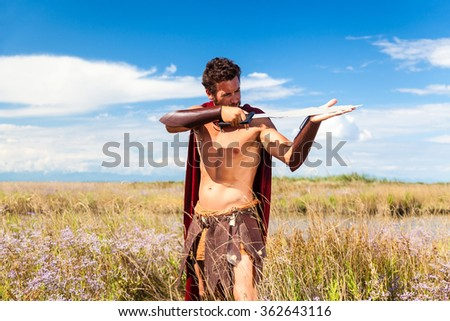 Portrait of ancient shirtless warrior with sword and red cloak. Spartan Soldier. Landscape background - stock photo