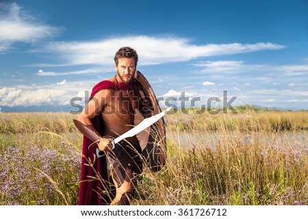 Portrait of ancient shirtless warrior with sword, shield and red cloak. Spartan Soldier. Landscape background - stock photo