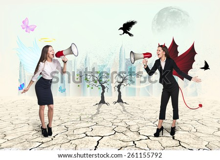 Portrait of angel and devil girls with megaphone in desert - stock photo