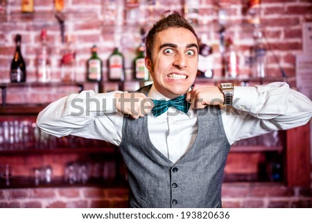 Portrait of angry and stressed bartender or barman with bowtie behind the bar with alcoholic drinks around - stock photo
