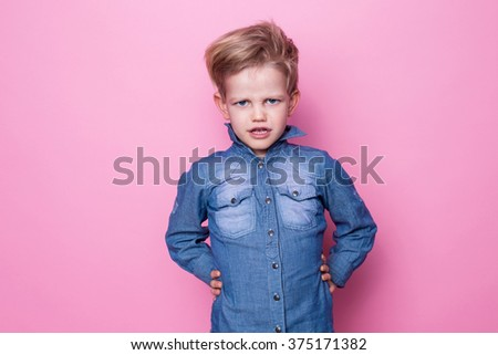 Portrait of angry beautiful little boy. Studio portrait over pink background - stock photo