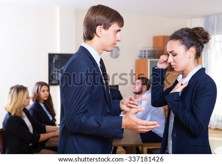 Portrait of angry boss and upset employee in the office interior  - stock photo
