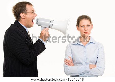 Portrait of angry boss shouting at his secretary through megaphone who is indifferent to it - stock photo