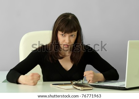 Portrait of angry businesswoman knocks fists