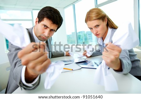 Portrait of angry employees with papers in hands looking at camera strictly - stock photo
