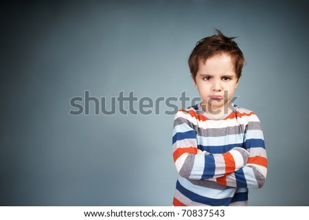 Portrait of angry little boy on blue background - stock photo