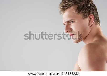 Portrait of Angry Looking Handsome Caucasian Man With Naked Torso. Posing Against Gray Background. Horizontal Image Orientation - stock photo
