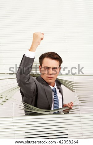Portrait of angry man looking at camera out of venetian blind and showing fist - stock photo