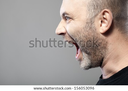 portrait of angry man s?reaming isolated on gray background with copyspace - stock photo