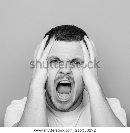 Portrait of angry man screaming and pulling hair - Monochrome or black and white portrait - stock photo