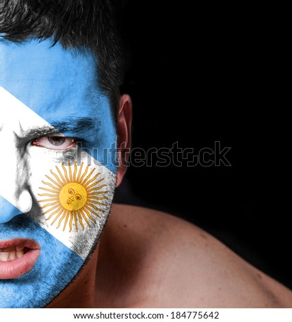 Portrait of angry man with painted flag of Argentina - stock photo