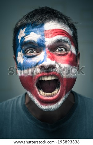 Portrait of angry man with USA flag painted on face. - stock photo