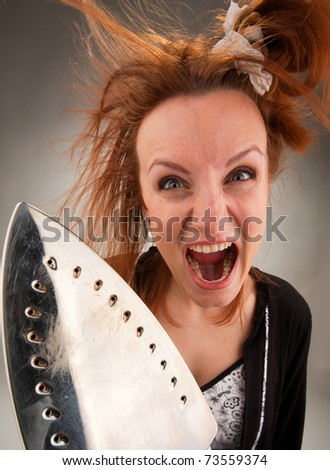 Portrait of angry screaming housewife with steam iron - stock photo