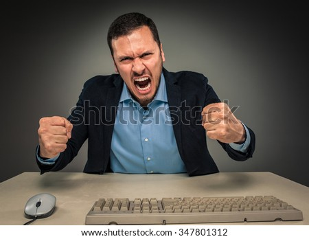 Portrait of angry upset young man in blue shirt and jacket with fists up yelling sitting at a desk near a computer isolated on gray background. Negative human emotion, facial expression. Closeup  - stock photo