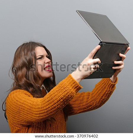 Portrait of angry woman screaming at  her laptop against gray background - stock photo
