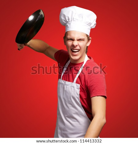 portrait of angry young cook man hitting with pan over red background - stock photo