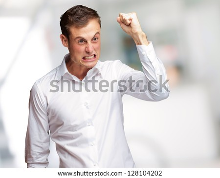 Portrait Of Angry Young Man Clenching His Fist, Outdoor - stock photo