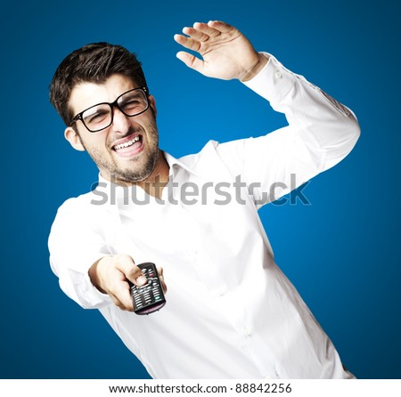 portrait of angry young man using tv control over blue background - stock photo