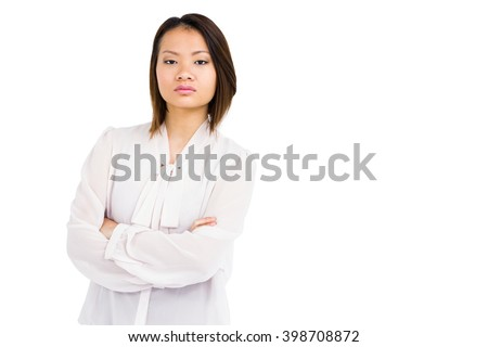 Portrait of angry young woman standing with arms crossed on white background - stock photo