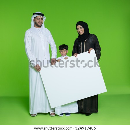 Portrait of Arab family holding blank placard - stock photo