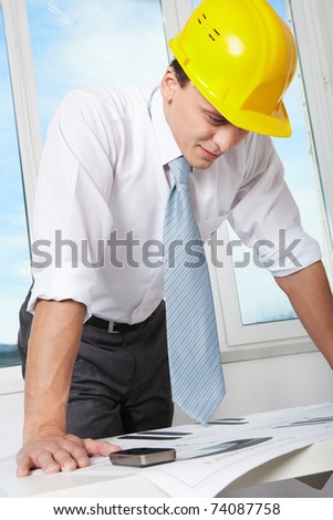 Portrait of architect in helmet looking at blueprint in office - stock photo