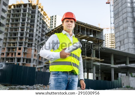 Portrait of architect in red hardhat posing on building site - stock photo
