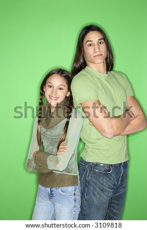 Portrait of Asian-American girl and teen boy standing back to back against green background. - stock photo