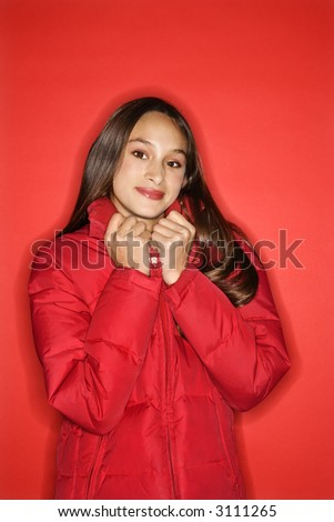 Portrait of Asian-American teen girl holding collar of her coat and smiling standing against red background. - stock photo