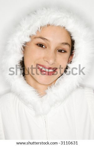 Portrait of Asian-American teen girl wearing fur lined coat hood and smiling against white background. - stock photo