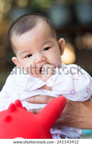 portrait of asian baby girl put her finger in mouth