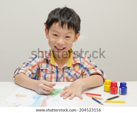 Portrait of Asian boy looking happy after finishing his artwork  - stock photo