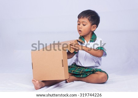 portrait of asian boy play brown box on white background