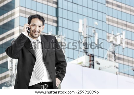 Portrait of asian businessman in suit outdoors,talking on the phone - stock photo