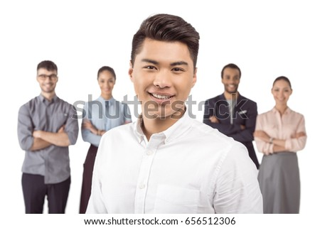 portrait of asian businessman standing in front of his colleagues isolated on white