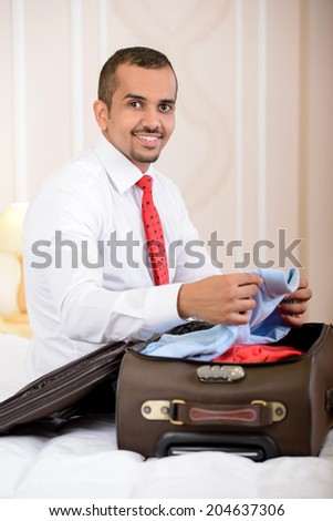Portrait of Asian businessman with a suitcase, sitting on the bed and makes things up a suitcase in hotel room - stock photo
