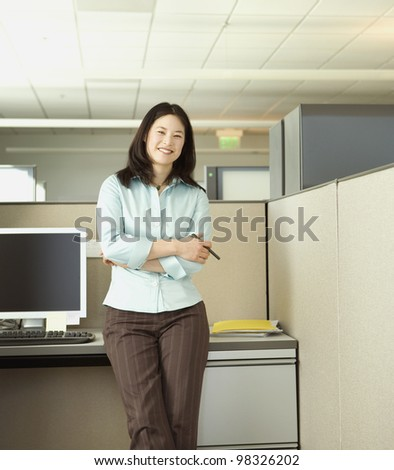 Portrait of Asian businesswoman in cubicle - stock photo