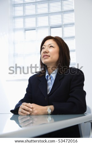 Portrait of Asian businesswoman sitting at desk. - stock photo