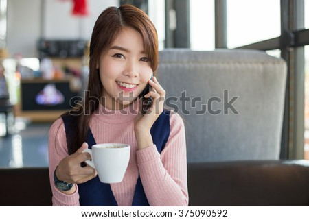 Portrait of asian businesswoman using a smart phone in a cafe.