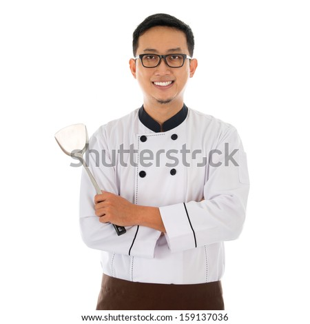Portrait of Asian chef holding spatula, smiling and standing isolated on white background. - stock photo