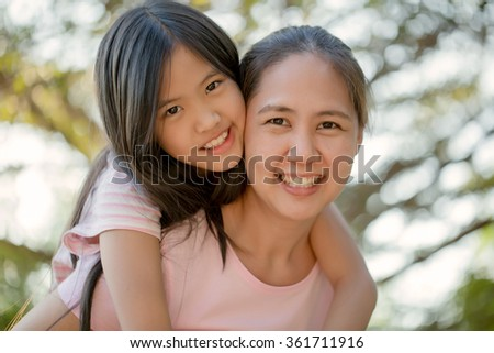 Portrait of Asian daughter with mother in the park - stock photo