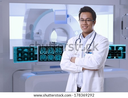 Portrait of asian doctor in MRI room at hospital, looking at camera, smiling. - stock photo