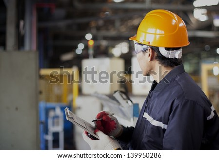 Portrait of asian engineer standing in the factory - stock photo