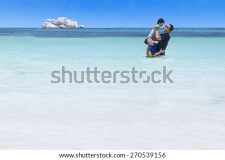 Portrait of asian father playing with his children on the tropical beach - stock photo