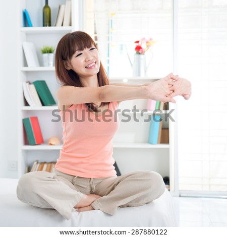 Portrait of Asian girl stretching arms in the morning on her bed. Young woman indoors living lifestyle at home.