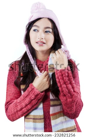 Portrait of asian girl wearing winter knitted clothes with shawl and hat, isolated on white