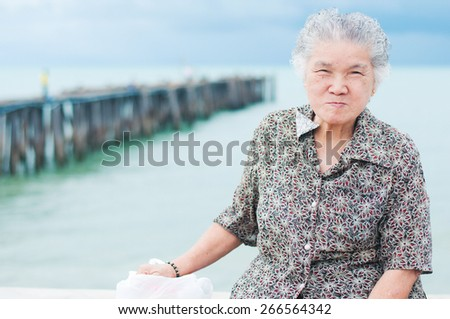 Portrait of asian grandma smile happiness with sea background - stock photo