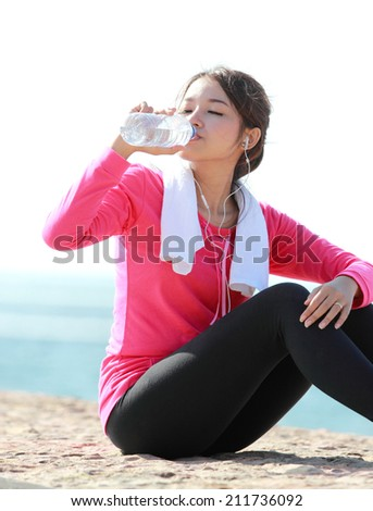 Portrait of asian healthy fitness woman drinking a bottle of water - stock photo
